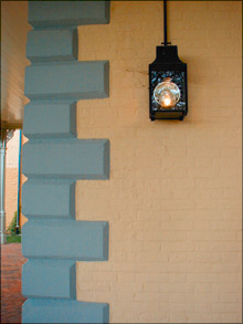 Color photo of old fashioned outdoor light affixed to yellow brick wall of Belmont Mansion.