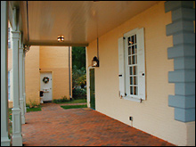 Color photo of red brick walkway next to house with yellow walls, a large window and a roof over the walkway.